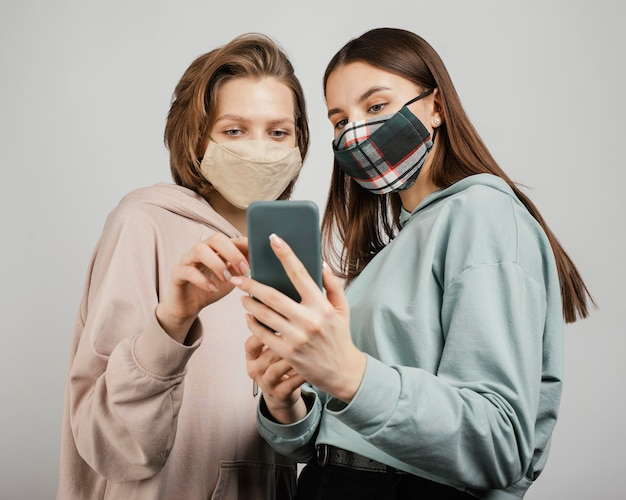 Amici femminili che indossano maschere e utilizzando il telefono