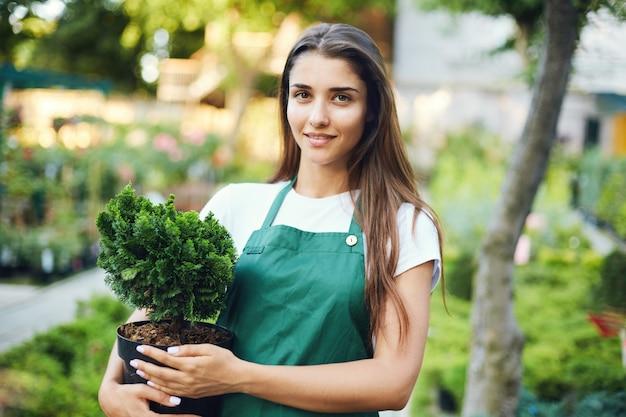 Giardiniere femminile che tiene un albero dei bonsai in una pentola che guarda l'obbiettivo. proprietario di un negozio di forniture e piante da giardino all'aperto.
