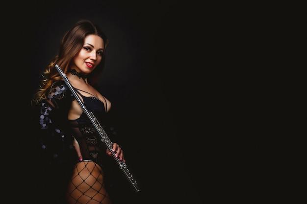 Artista ragazza femminile in tuta con flauto su sfondo nero. flauto in mano. giocatore con strumento orchestra. isolato su nero. il concetto di poster musicale