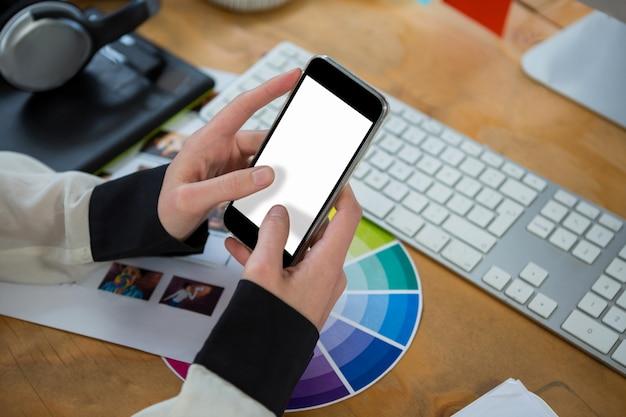 Designer grafico femminile utilizzando il telefono cellulare allo scrittorio