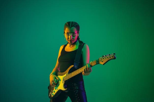 Ritratto femminile del chitarrista isolato sulla parete verde dello studio nella luce al neon
