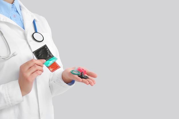 Ginecologo femminile con i preservativi su priorità bassa bianca