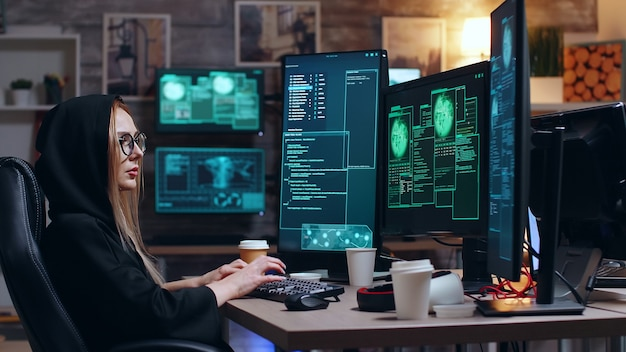 Hacker femminile che indossa una felpa con cappuccio che utilizza un virus pericoloso per rendere vulnerabile il database del governo.