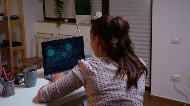Hacker femminile che lavora da casa utilizzando un virus pericoloso per rendere vulnerabile il database del governo. programmatore che scrive un malware per attacchi informatici utilizzando un dispositivo ad alte prestazioni durante la mezzanotte.