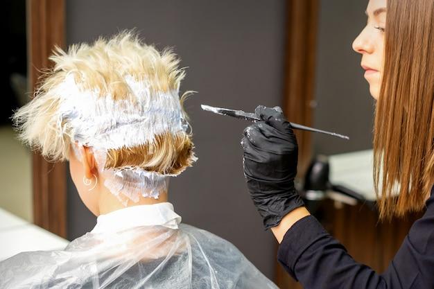 Parrucchiere femminile che tinge i capelli biondi corti di una giovane donna in un parrucchiere