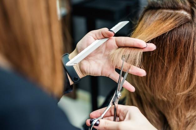 Il parrucchiere femminile sta tagliando la fine dei capelli della donna su.