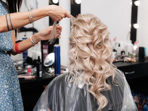 Un parrucchiere femminile fa un'acconciatura festosa per una bionda in un salone di bellezza