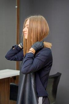 Il parrucchiere femminile indossa il grembiule nero in un parrucchiere