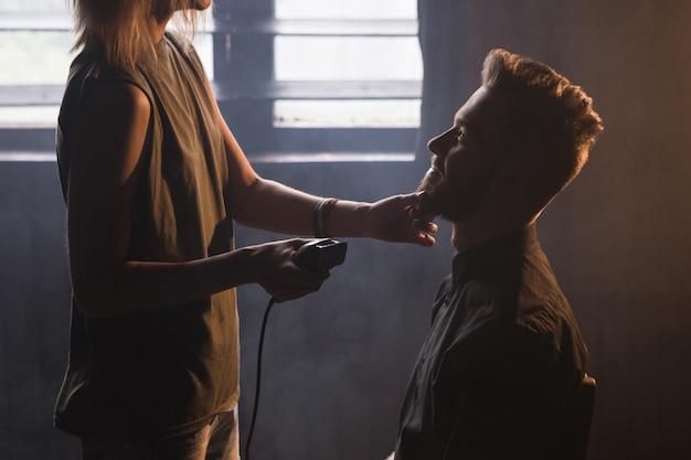 Parrucchiere femminile che rade la barba dell'uomo alla moda. barbiere atmosferico sfondo scuro, sorridente giovane maschio alla moda a fuoco in primo piano, donna irriconoscibile con rasoio elettrico