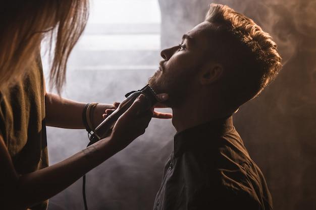Parrucchiere femminile che rade il primo piano alla moda dell'uomo. barbiere atmosferico con fumo bianco, giovane maschio alla moda a fuoco in primo piano, donna irriconoscibile con rasoio elettrico