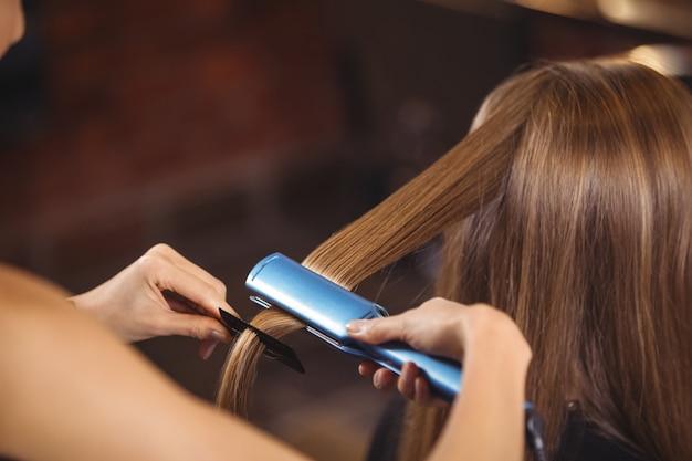 Parrucchiere femminile che raddrizza i capelli di un cliente