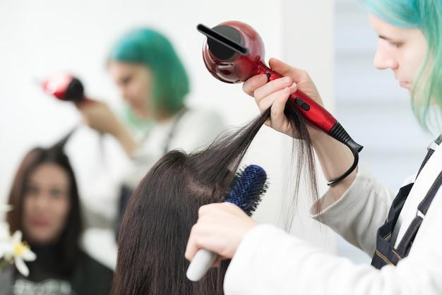 L'hairstylist femminile asciuga i capelli castani con l'asciugacapelli rosso e la spazzola per capelli blu nella bellezza professionale...