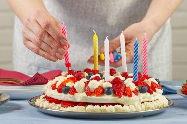 La mano femminile aggiunge le candele di compleanno alla torta di fragole fatta in casa e alle candele di compleanno