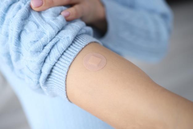 Mano femminile dopo la vaccinazione con cerotto sigillato. la vaccinazione e il suo concetto di conseguenze
