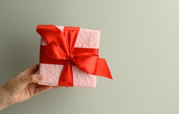 La mano femminile sta tenendo una scatola regalo rosa su uno sfondo grigio, buon compleanno concept