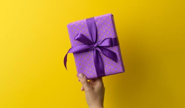 La mano femminile tiene in mano una confezione regalo purole su uno sfondo giallo, buon compleanno concept