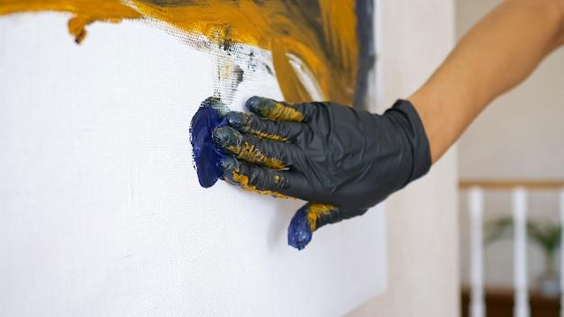 La mano femminile in un guanto di gomma nera corre su tela bianca disegnando onde blu in atelier con pareti bianche sotto un primo piano di luce intensa
