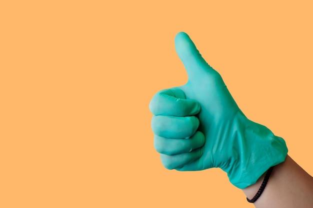 La mano femminile in guanto di lattice blu fa i pollici in su come un gesto