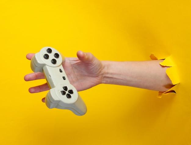 La mano femminile cattura il gamepad attraverso carta gialla strappata. concept creativo minimalista