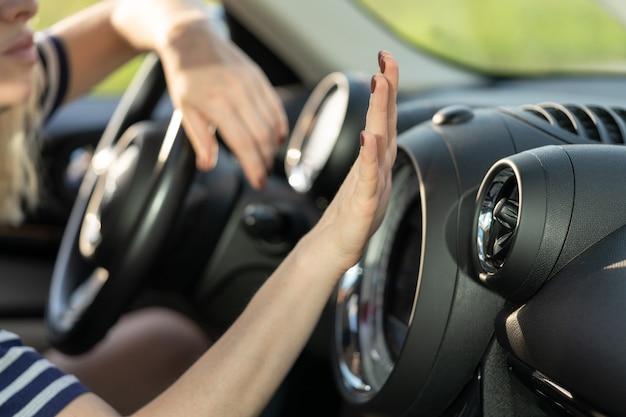 Pannello di controllo dell'aria condizionata della mano femminile nell'automobilista che tiene la mano al sistema di condizionamento