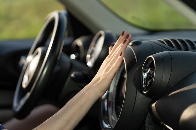 Mano femminile controlla il pannello dell'aria condizionata nell'automobilista che tiene la mano al sistema di condizionamento