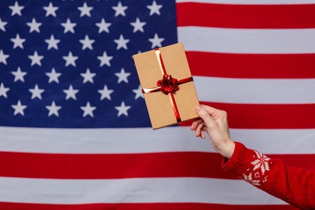 Mano femminile in maglione di natale tiene confezione regalo sulla bandiera usa