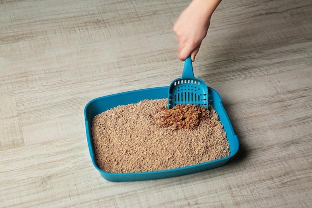Lettiera per gatti per la pulizia delle mani femminili su fondo in legno