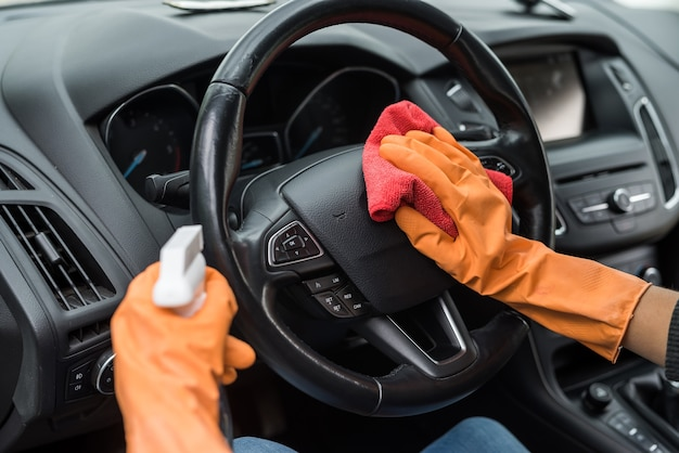 Mano femminile che pulisce l'interno della sua auto dal coronavirus e dalla pandemia con liquido disinfettante vechile