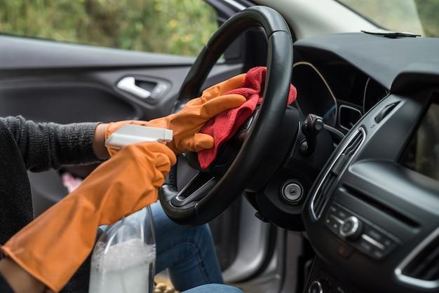 Mano femminile che pulisce l'interno della sua auto dal coronavirus e dalla pandemia