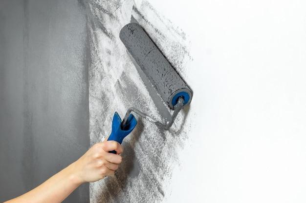 Il primo piano femminile della mano dipinge una parete nel gray. il concetto di riparazione, cambiamento, design