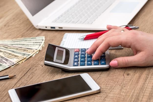 Mano femminile che conta qualcosa sul fondo della tavola in legno del calcolatore