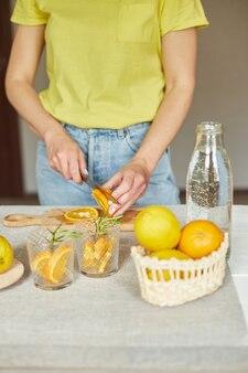 Arancia tagliata a mano femminile, donna che prepara, prepara una limonata fresca di agrumi e rosmarino in vetro su un tavolo bianco a casa, bevanda estiva, acqua salutare disintossicante.