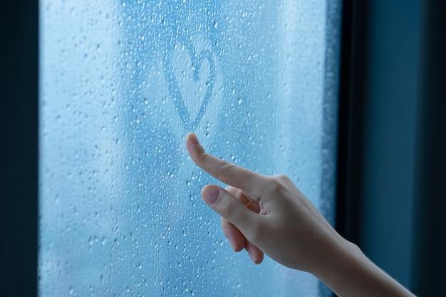 Mano femminile disegna un cuore su una finestra nebbiosa durante la pioggia. bicchiere in gocce d'acqua