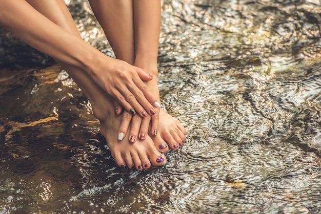 Chiodi femminili della pittura di arte del dito dei piedi e della mano su acqua