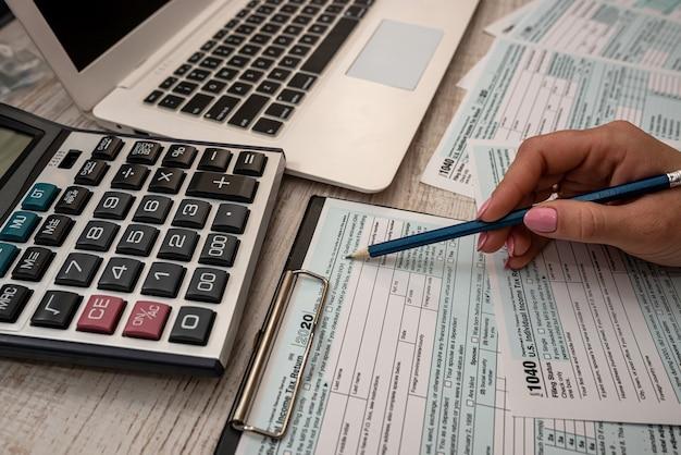 Mano femminile che compila il modulo fiscale statunitense 1040 con calcolatrice di aiuto e laptop in ufficio