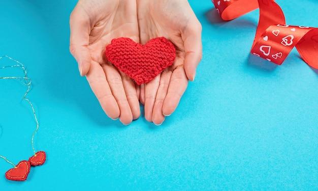 La mano femminile dà un cuore lavorato a maglia