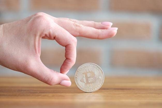 Mano femminile che dà clic al primo piano della moneta bitcoin d'argento