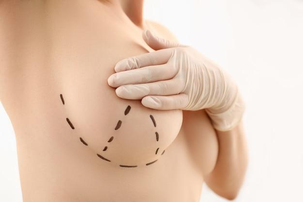Mano femminile in guanti che tengono il primo piano del seno