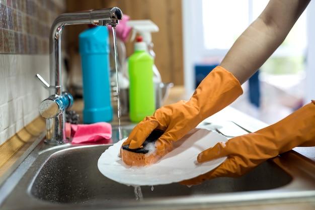 Mano femminile in guanti che lavano i piatti sopra il lavandino in cucina. lavori di casa