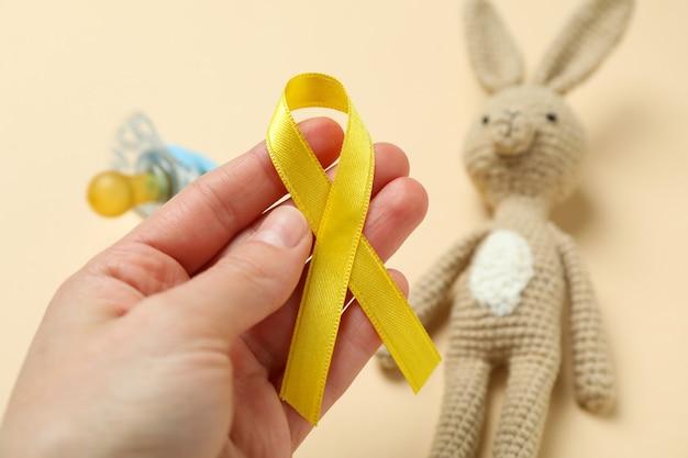 Nastro di consapevolezza del cancro dell'infanzia della stretta della mano femminile, fine su