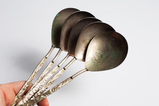 Mano femminile tenere una collezione di cucchiai antichi. sulla superficie del bianco.