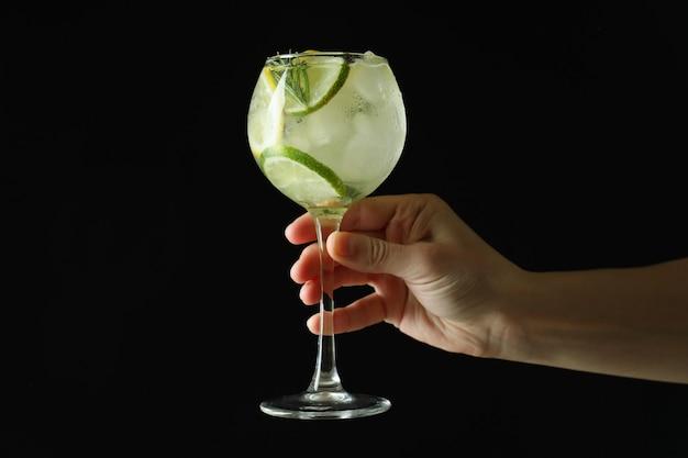 Mano femminile tenere un bicchiere di cocktail con agrumi su sfondo scuro