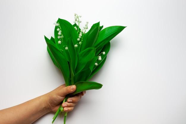 La mano femminile tiene un bouquet di mughetto sullo sfondo bianco isolato primavera o madri da...