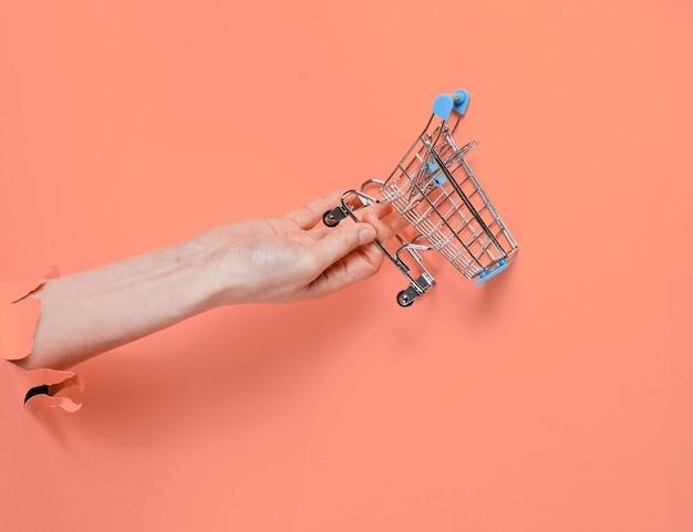 Mini carrello della spesa della stretta della mano femminile attraverso carta rosa strappata. concetto di acquisto minimalista