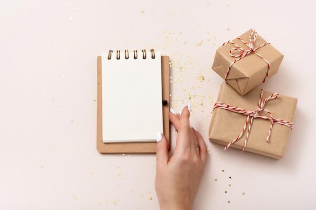 Modello femminile della carta in bianco del taccuino della tenuta della mano, coriandoli dorati delle stelle, scatole regalo su fondo beige. lay piatto, vista dall'alto, copia spazio, minimalista. composizione nel nuovo anno di natale.