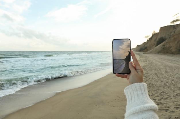 Telefono femminile della stretta della mano con la fabbricazione del selfie sul mare