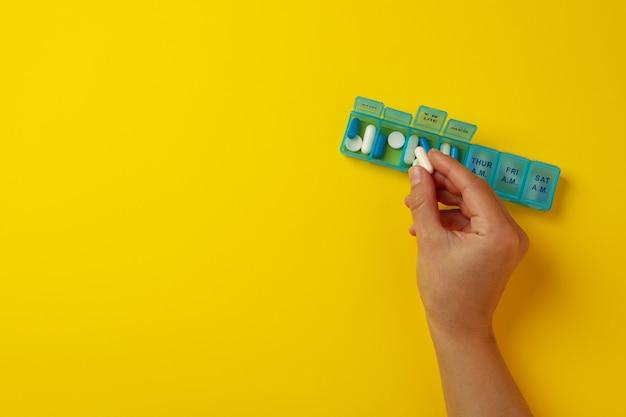 Pillola femminile della stretta della mano su colore giallo con il contenitore con le pillole