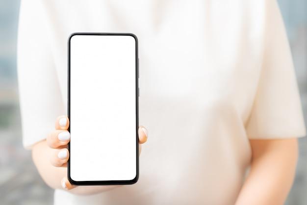 La mano femminile tiene lo smart phone con lo schermo in bianco dello spazio della copia per il vostro messaggio di testo o contenuto informativo, modello