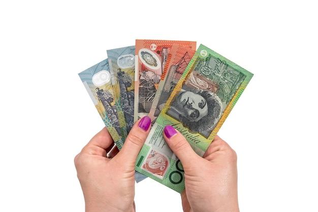 Mano femminile che tiene dollaro australiano isolato su priorità bassa bianca
