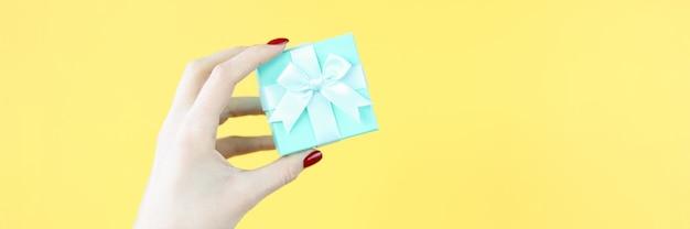 Mano femminile che tiene bellissimo regalo blu su sfondo giallo closeup confezione regalo concept